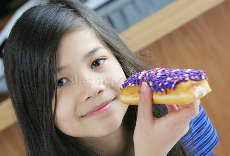 Kind dat doughnut eet stock foto's