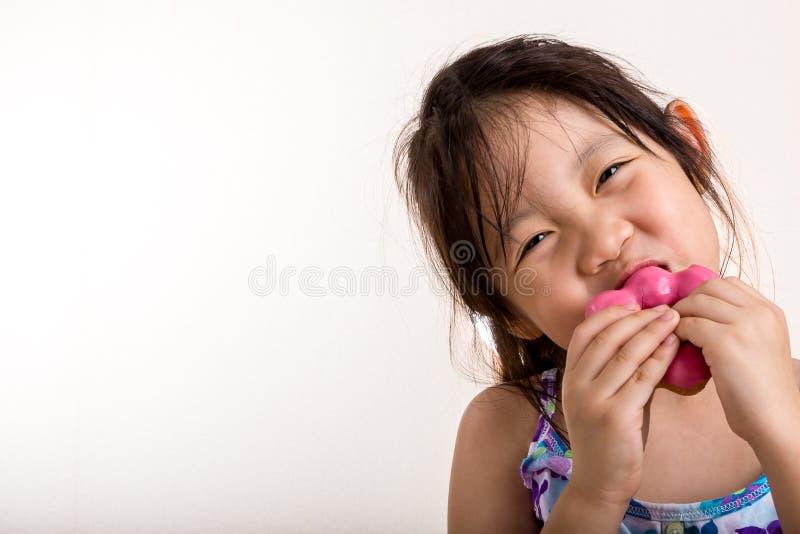 Kind dat doughnut eet stock afbeelding