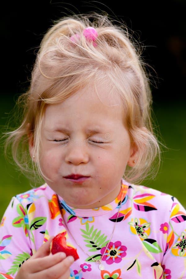 Kind dat een aardbei in de tuin eet stock afbeelding