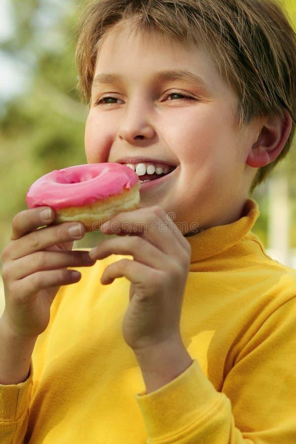 Kind Dat Een Roze Doughnut Eet Stock Foto