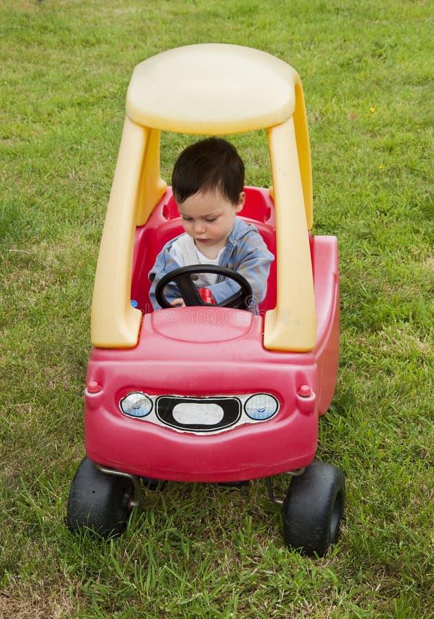 Kind dat een stuk speelgoed auto drijft stock afbeelding