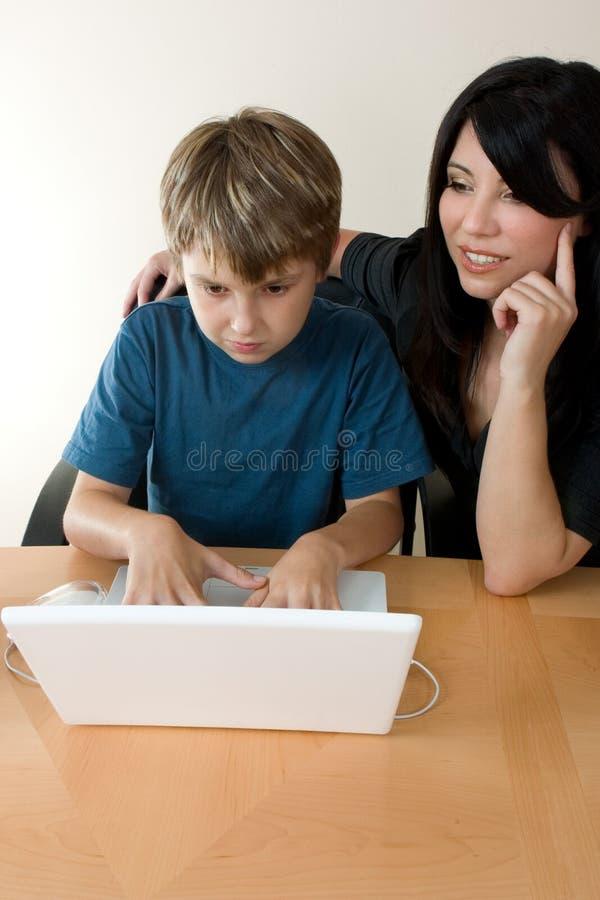 Kind dat laptop met behulp van terwijl de volwassene controleert stock foto's