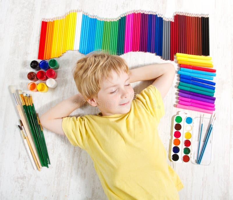 Kind dat naast potloden, borstels, verven droomt royalty-vrije stock afbeelding