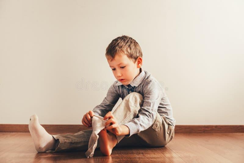 Kind dat op de grond zit en zijn sokken aandoet met een uitdrukking van inspanning, een concept van autonomie stock fotografie