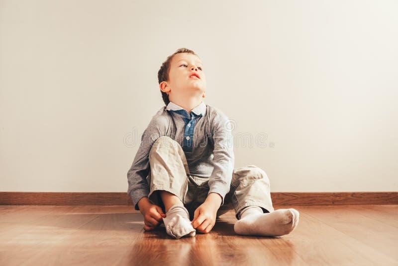 Kind dat op de grond zit en zijn sokken aandoet met een uitdrukking van inspanning, een concept van autonomie royalty-vrije stock afbeelding