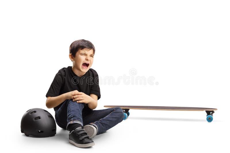 Kind dat op de grond zit huilend en knie vasthoudt, gewond van een skateboard stock afbeeldingen