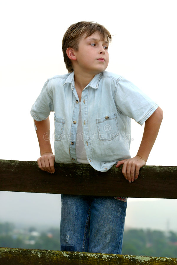 Kind dat op een omheining leunt stock afbeelding