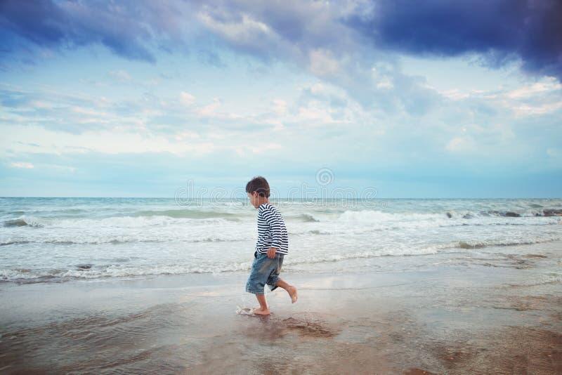 Kind dat op het strand loopt De vakantie van de zomer het gelukkige jong geitje spelen op strand in de zonsondergangtijd stock fotografie