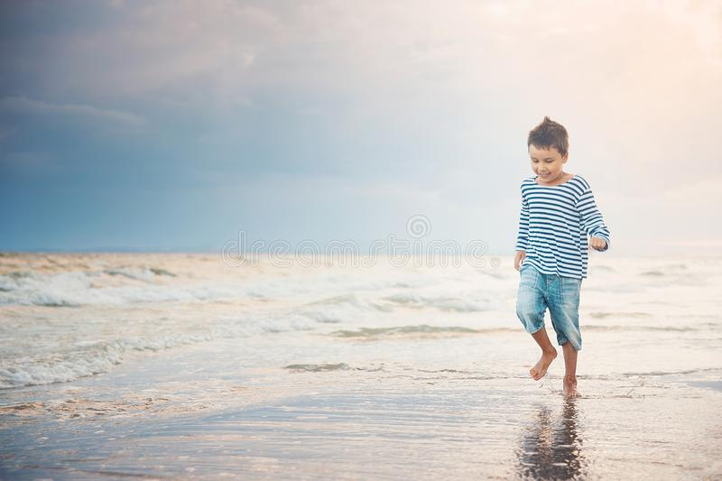 Kind dat op het strand loopt De vakantie van de zomer het gelukkige jong geitje spelen op strand in de zonsondergangtijd royalty-vrije stock fotografie