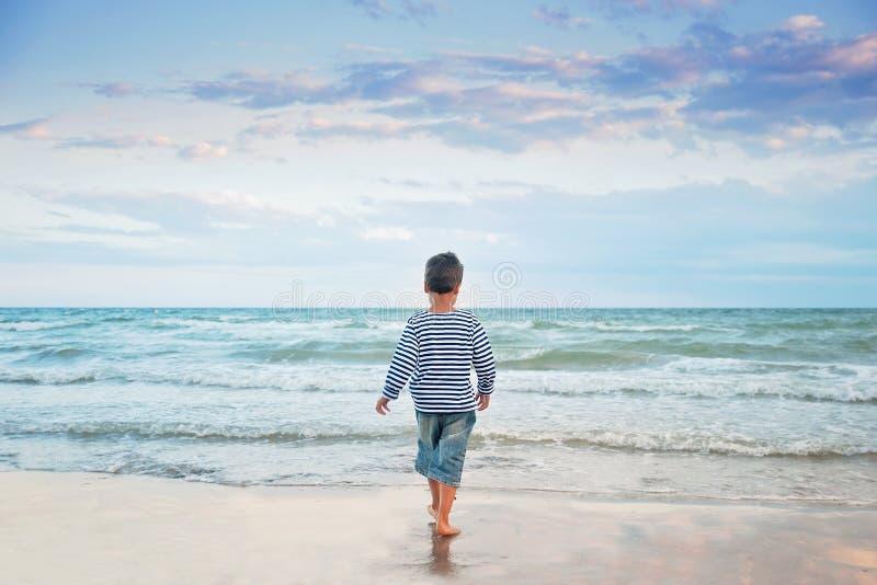 Kind dat op het strand loopt De vakantie van de zomer het gelukkige jong geitje spelen op strand in de zonsondergangtijd stock afbeeldingen