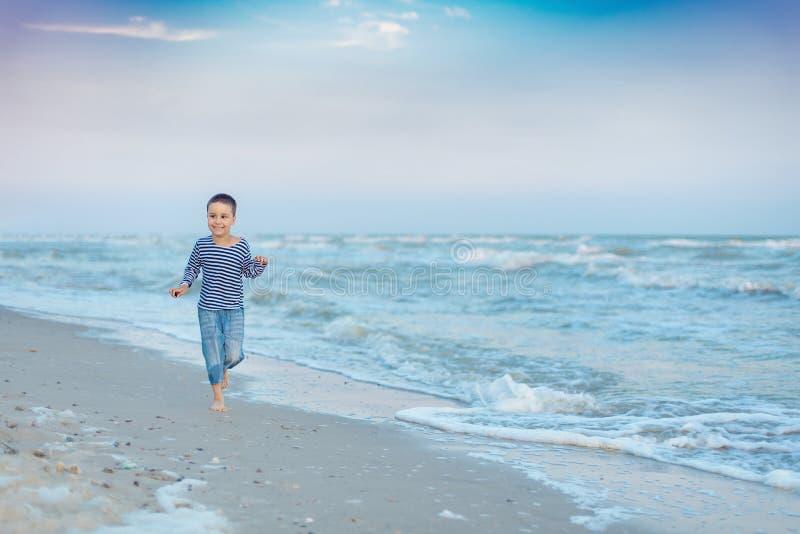 Kind dat op het strand loopt De vakantie van de zomer het gelukkige jong geitje spelen op strand in de zonsondergangtijd stock foto