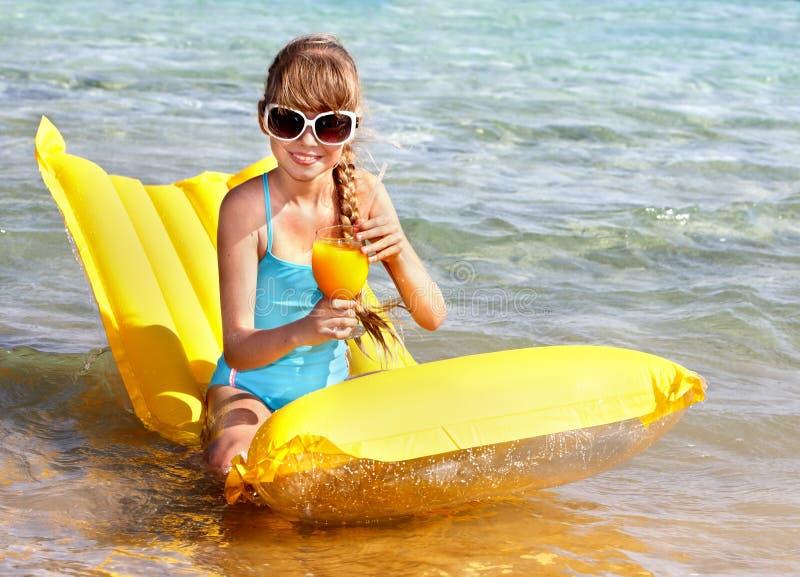 Kind dat op opblaasbare strandmatras zwemt. stock afbeeldingen