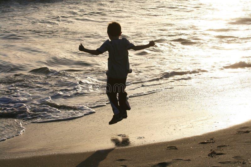 Kind dat op strand springt royalty-vrije stock afbeeldingen