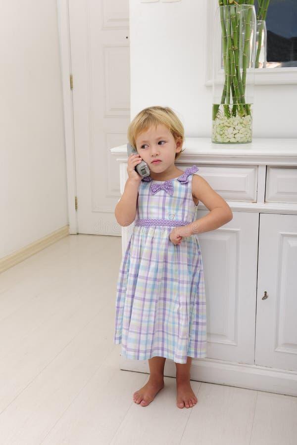Kind dat op telefoon thuis spreekt royalty-vrije stock afbeeldingen