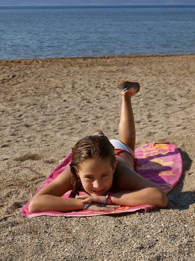 Kind dat op zandig strand ligt stock afbeeldingen