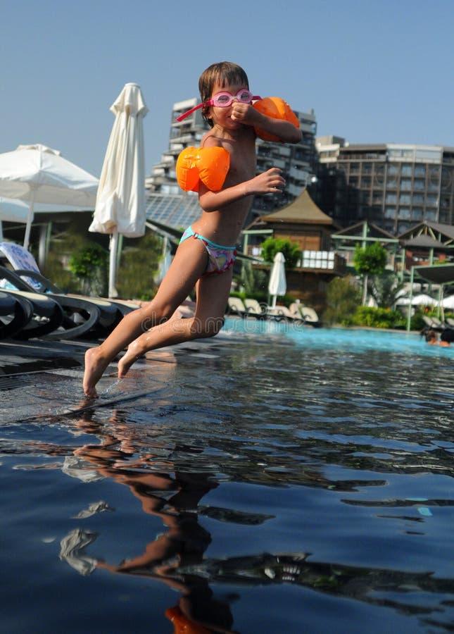 Kind dat in pool springt royalty-vrije stock afbeelding