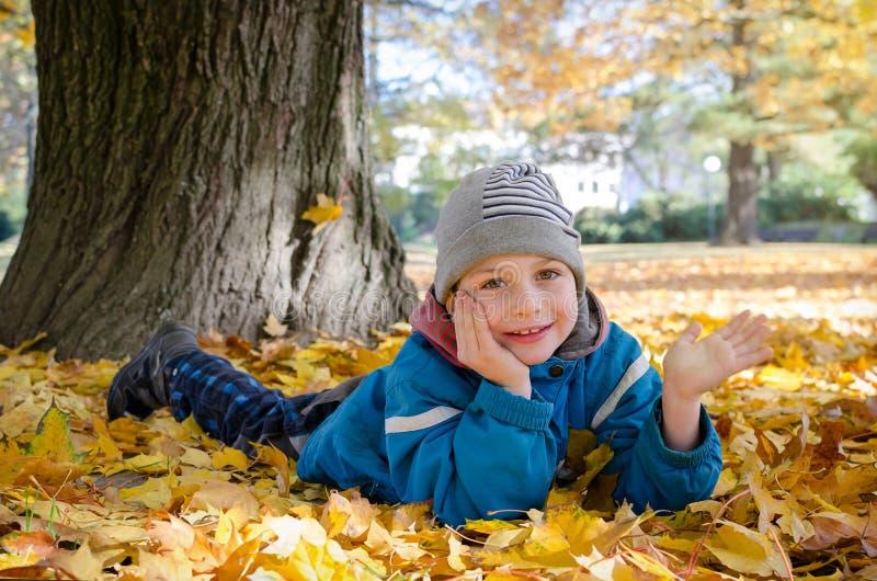 Kind in de herfst of dalingspark stock foto