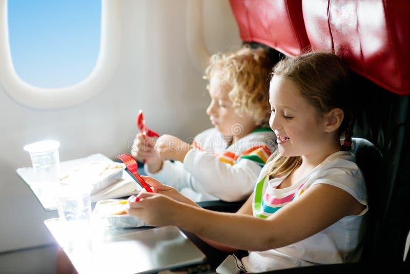 Kind in de zetel van het vliegtuigvenster De maaltijd van de jonge geitjesvlucht De kinderen vliegen Speciale inflight menu, voed royalty-vrije stock afbeelding