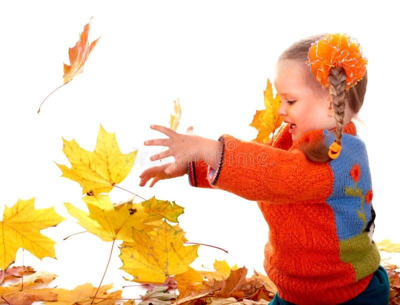 Kind in den orange Blättern des Herbstes. stockfotos