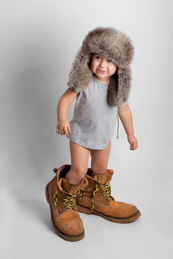 Kind in den Schuhen und im Hut des Erwachsenen lizenzfreie stockfotografie