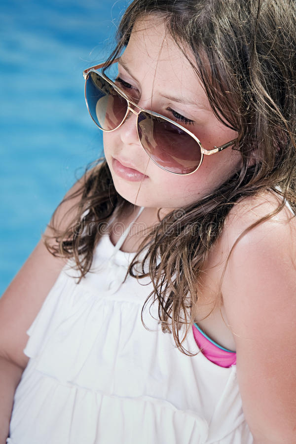 Kind in den Sonnenbrillen, die nahe bei dem Pool sitzen stockfotos