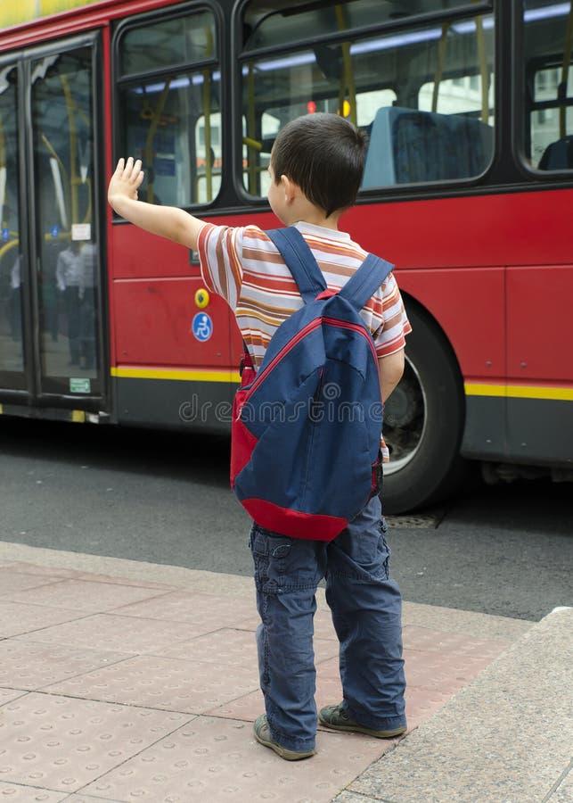 Kind an der Bushaltestelle lizenzfreie stockfotos