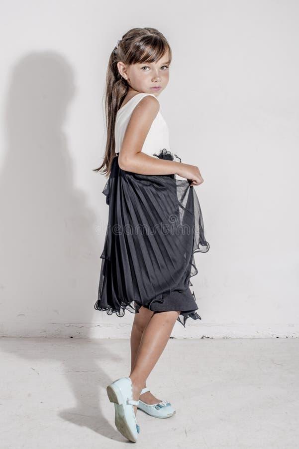 Kind des jungen Mädchens in einem festlichen Schwarzweiss-Kleid mit brunettte Haar stockbilder