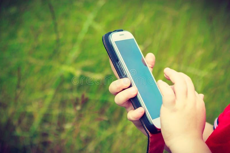 Kind des kleinen Jungen, das Spiele am Handy im Freien spielt stockfoto