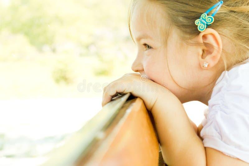 Kind des kleinen Mädchens, das über einem Geländer schaut lizenzfreie stockfotos