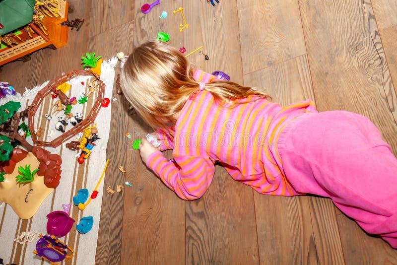 Kind des kleinen Mädchens, das zuhause mit vielen bunten Plastikspielwaren auf Bretterboden spielt stockbild
