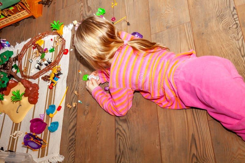 Kind des kleinen Mädchens, das zuhause mit vielen bunten Plastikspielwaren auf Bretterboden spielt stockfoto