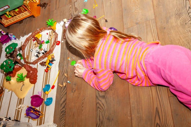 Kind des kleinen Mädchens, das zuhause mit vielen bunten Plastikspielwaren auf Bretterboden spielt stockfotografie