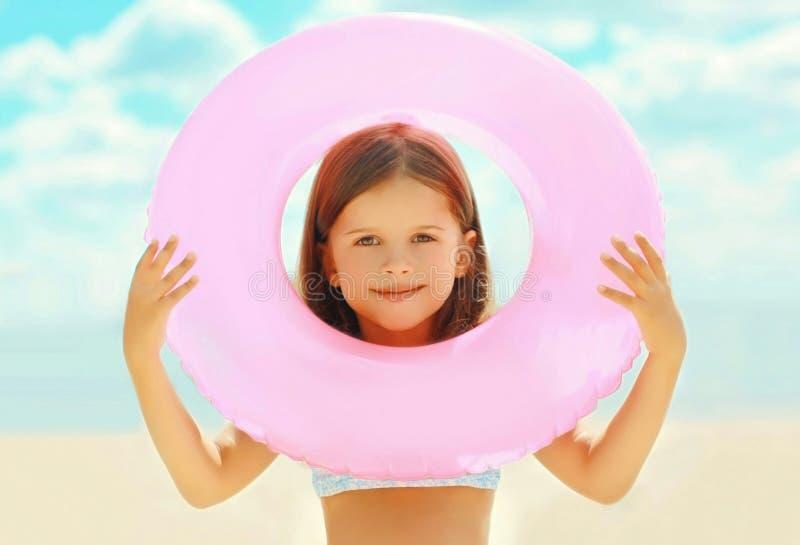 Kind des kleinen Mädchens der Sommerporträtnahaufnahme mit aufblasbarem Kreis auf Sommerstrand lizenzfreie stockfotografie