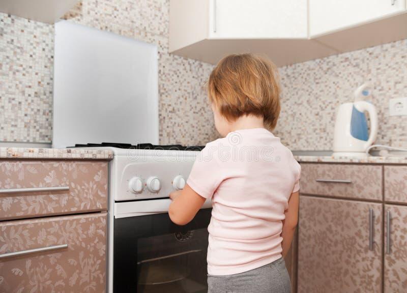 Kind dichtbij fornuis bij binnenlandse keuken stock foto's