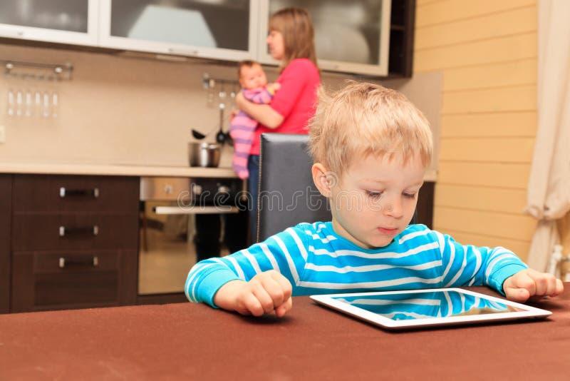 Kind die aanrakingsstootkussen bekijken terwijl de moeder thuis kookt stock foto