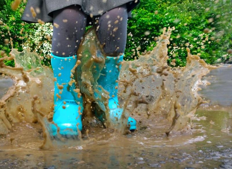 Kind die blauwe regenlaarzen dragen die in een vulklei springen royalty-vrije stock foto's