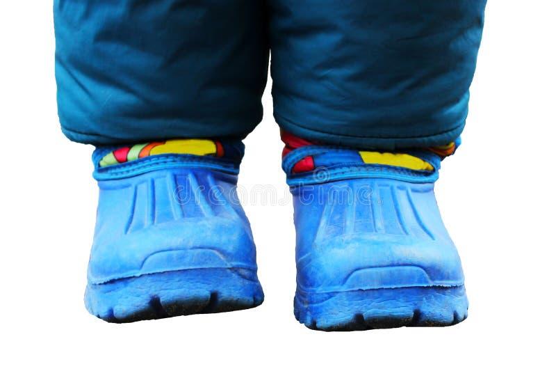 Kind die blauwe regenlaarzen dragen die in een vulklei springen Sluit omhoog stock afbeelding