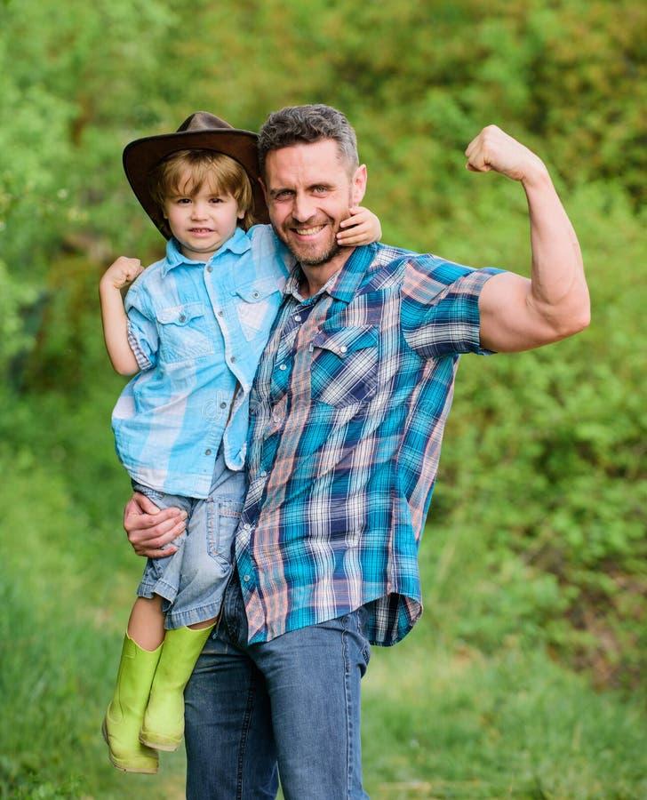 Kind die de papa van de pretcowboy hebben Rustieke familie Groeiende leuke cowboy Kleine helper in tuin Weinig jongen en vader in royalty-vrije stock fotografie