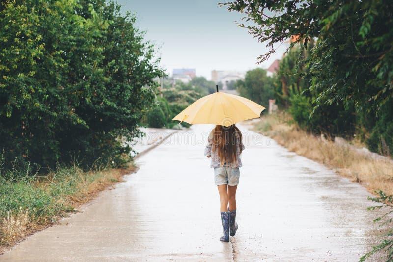 Kind die in de regen lopen stock foto