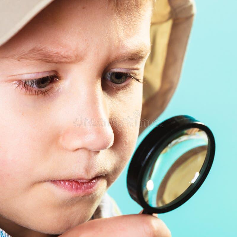 Kind die door een vergrootglas kijken stock foto's