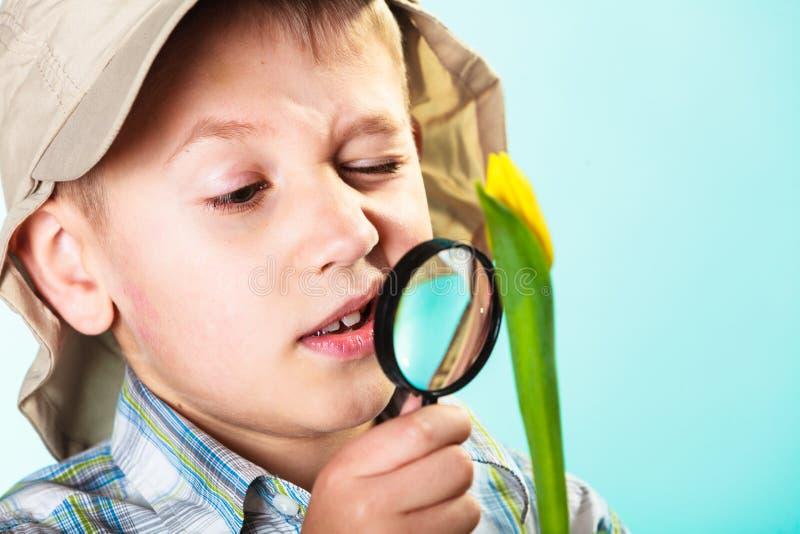 Kind die door een vergrootglas kijken stock afbeelding