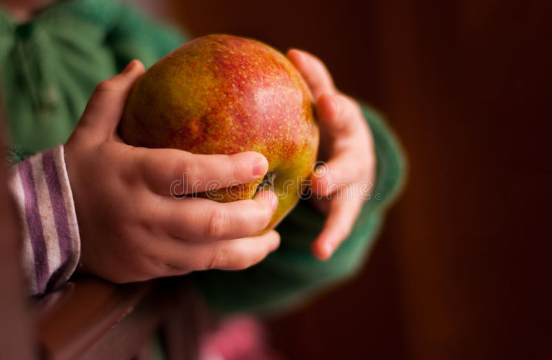 Kind die een appel in een hand houden stock foto