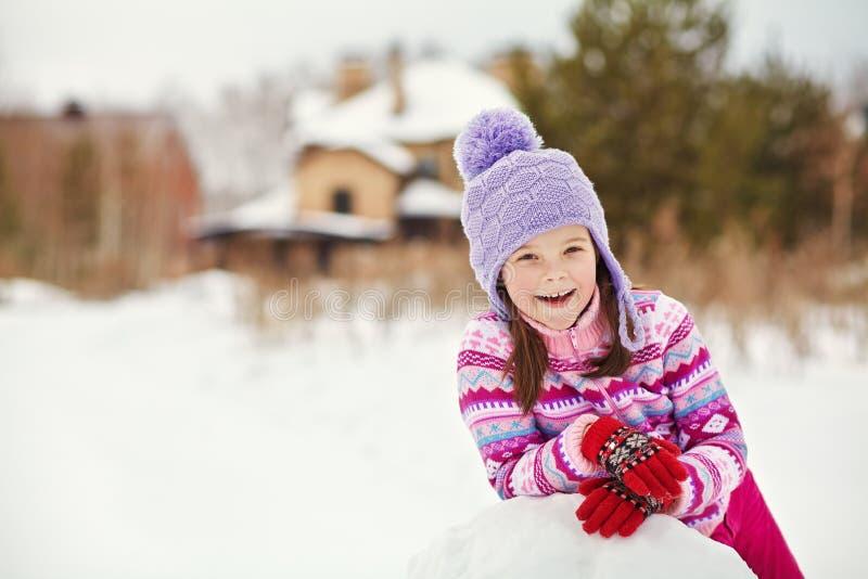 Kind die een sneeuwman bouwen stock afbeelding