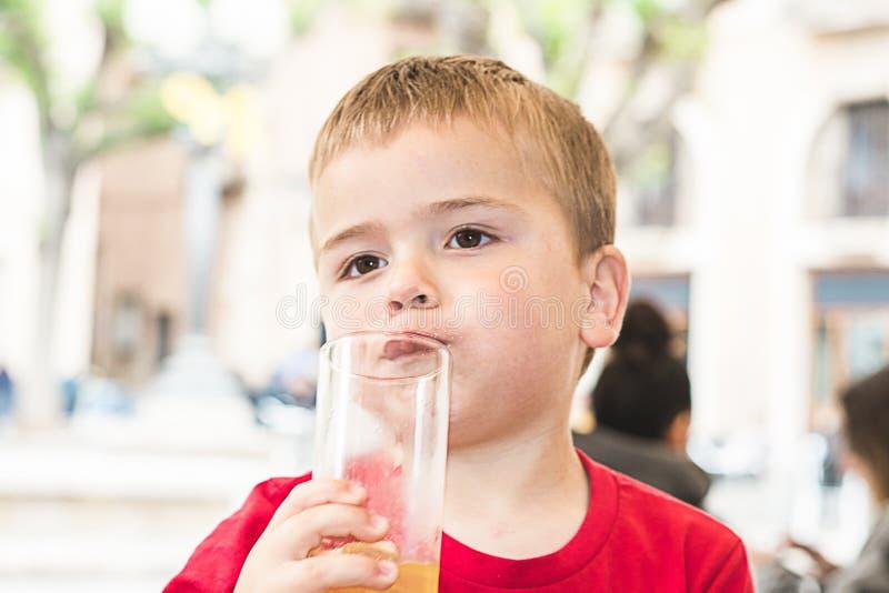 Kind die een soda in een glas drinken stock afbeeldingen