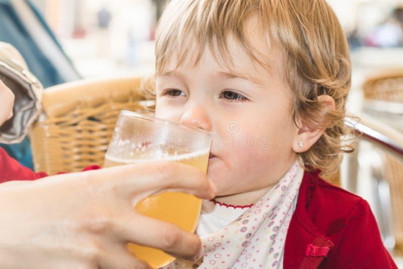 Kind die een soda in een glas drinken stock afbeelding