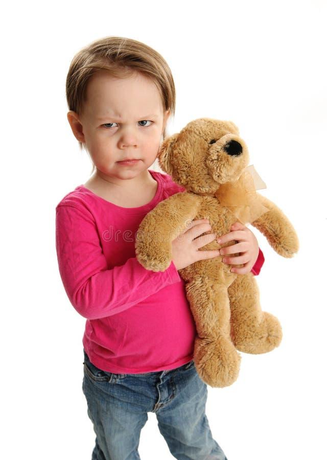 Kind die een teddybeer met gekke uitdrukking houden stock afbeeldingen
