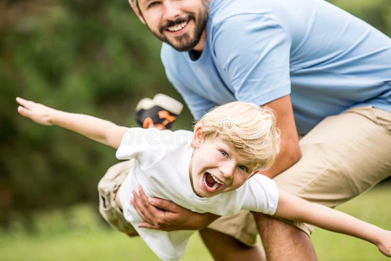 Kind die en met vader lachen spelen stock afbeeldingen
