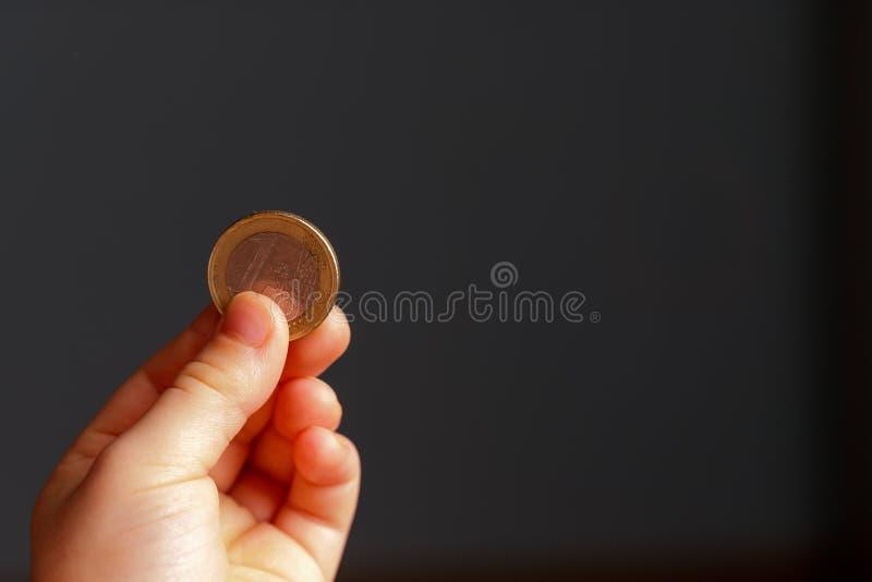 Kind die euro muntstuk in zijn hand houden Het beeld van de kleingeldvoorraad Slechte laag inkomensgroep Donkere achtergrond - Be stock afbeeldingen