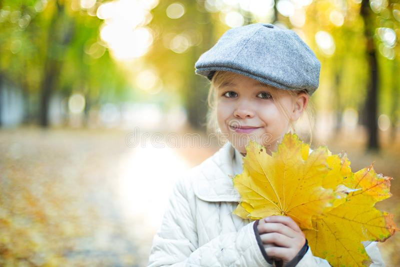 Kind die gele en rode bladeren houden Meisje met esdoornbladeren royalty-vrije stock foto's