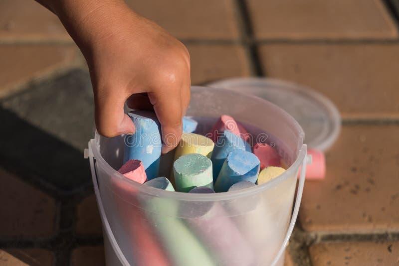 Kind die groot kleurenkrijt van de plastic emmer plukken royalty-vrije stock afbeeldingen